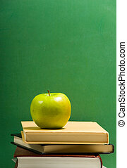School books on green with apple