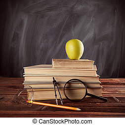School books with accessories placed on wooden table