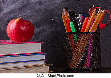 School books with apple on desk