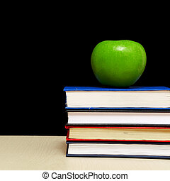 School books with apple on desk,