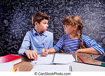 School boy and girl at the desk, big blackboard