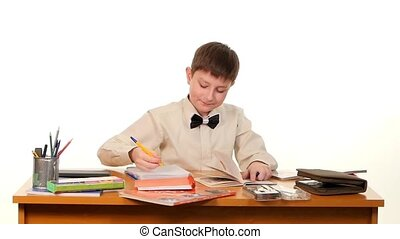 School boy doing his homework thinking about the topic of essay on white background, slow motion