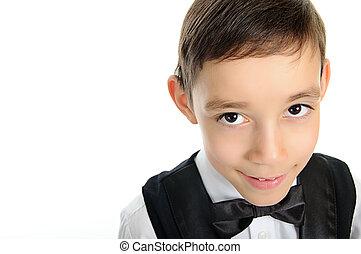 school boy in black suit with brown eyes looking at camera