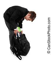 School boy packing school bag