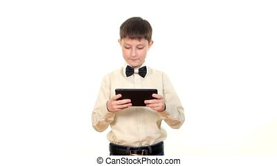 School boy playing something using tablet computer, on white background
