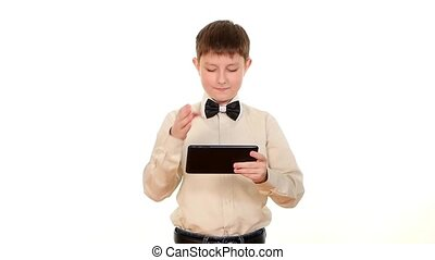 School boy playing something using tablet computer, on white background, slow motion