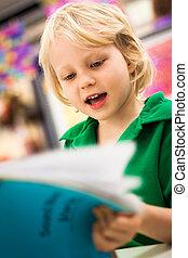 School boy reading a book