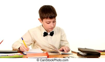 School boy sitting, thinking and writing homework in workbook using a book on white background