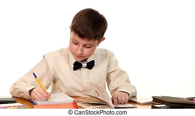 School boy sitting, thinking and writing homework in workbook using a book on white background, slow motion
