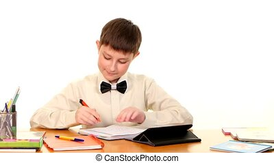 School boy sitting, thinking and writing homework in workbook using a tablet computer on white background