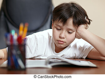 School boy studies hard over his book at home. - A teen...