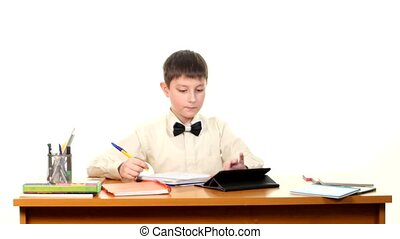 School boy taught lessons using the tablet computer doing homework on white background