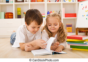 School boy teaching and showing her sister how to read -...