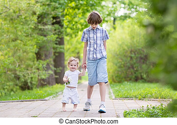 School boy walking with his little sister in a park