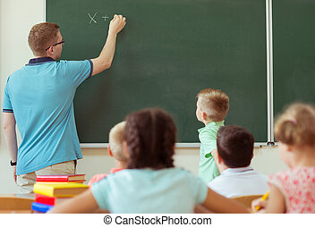 School boy with his teacher at the blackboard at math lesson in classroom at school