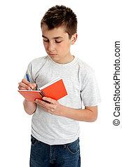 School boy writing in book