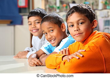 Well behaved and waiting patiently three smiling young school boys in classroom, focus point is on middle boy wearing blue