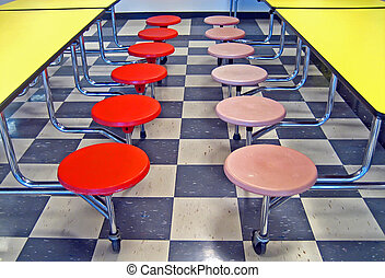 Pink and red/orange school cafeteria seats and yellow cafeteria tables.