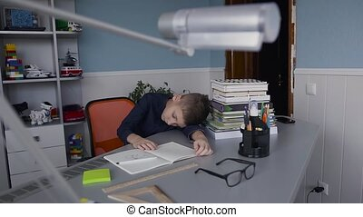School child do homework. The school boy does his homework at home, pupil has been bored on the lesson. Cute beautiful boy learning his lessons at home and sleeping at the table, back to school