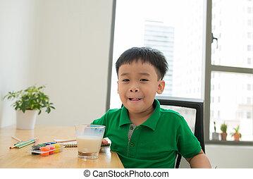 School child doing homework and drinking milk