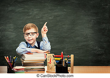 School Child in Classroom over Blackboard Background, Boy Advertising Pointing Finger to Blank Chalkboard
