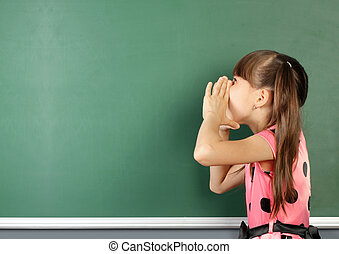 school child shouting near blank school blackboard, copy space