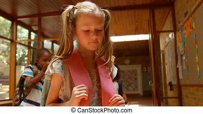 School children bullying a sad girl in corridor of ...