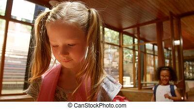 School children bullying a sad girl in the corridor of ...