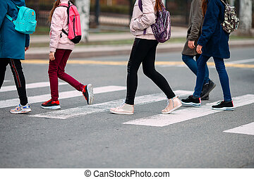 School children cross the road in medical masks. Children go to school