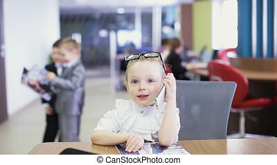 school children in classroom talking by phone