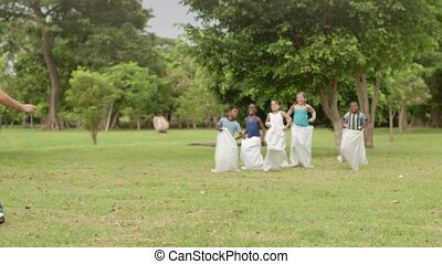 Elementary school teacher and kids having fun and playing sack race in city park