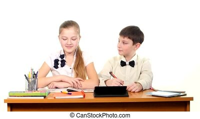 School children sitting by the table and doing homework, on white background