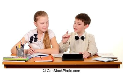 School children sitting by the table, doing homework and discussing something, on white background, slow motion