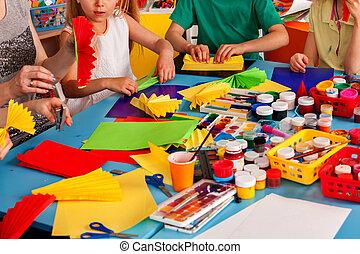 School children with scissors in kids hands cutting paper .
