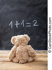 School class math. Teddy bear looking at a simple equation on a blackboard