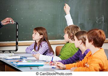 School class - Diligent student raising his hand in a school...