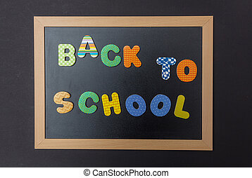 Black chalkboard with wooden frame, text back to school in colorful letters, black wall background