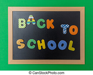 Black chalkboard with wooden frame, text back to school in colorful letters, green wall background