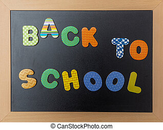 Black chalkboard with wooden frame, text back to school in colorful letters