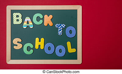 Green chalkboard with wooden frame, text back to school in colorful letters, red wall background