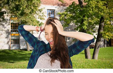 happy pretty teenage student girl holding head