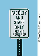 School faculty parking sign against a blue sky