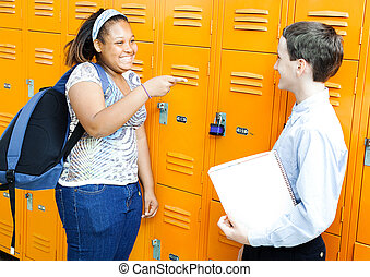 Middle school boy and girl laughing and joking together by their lockers.