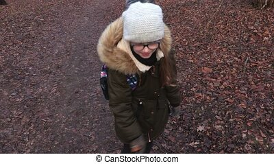 School girl child with backpack on path in the park