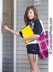 School Girl - Cute girl standing at door to a house carrying...