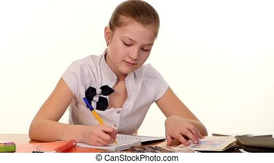School girl doing her homework and writes essay on white background, slow motion