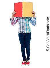 School girl hiding her face behind a notebook