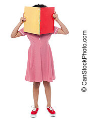 School girl hiding her face with a book - Shy little girl...