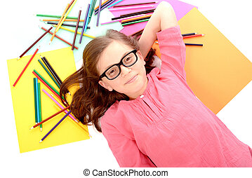 school girl lying on the floor with color pencils