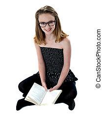 School girl sitting on floor holding book